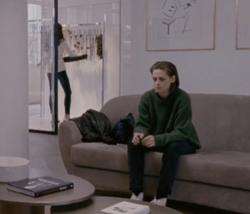 Maureen waits at a designer's showroom in her second shapeless sweater